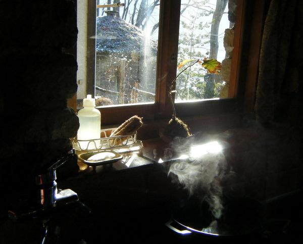 キッチンにくゆった湯気と窓越しの景色