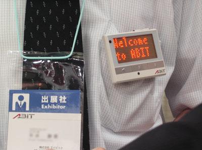 ABIT社のLEDコミュニケーションツールを胸ポケットに着けた男性
