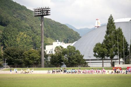 広い競技場を入場行進する 一列の大勢のチーム
