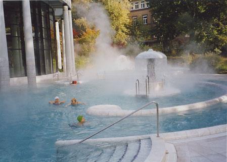 カラカラ浴場の屋外温泉の湯気の中で泳ぐ人々