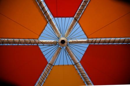 オレンジ色のテントの中から白い放射状パイプの天井を見る