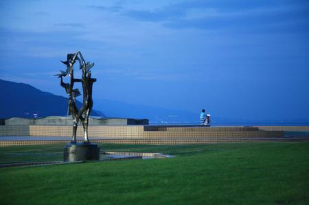 青一面の夕方 海の近くの芝生の公園に黒い彫刻