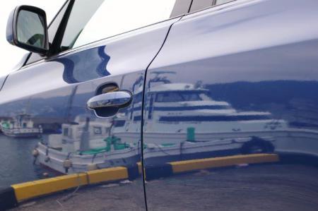車の側面に反射して写る船