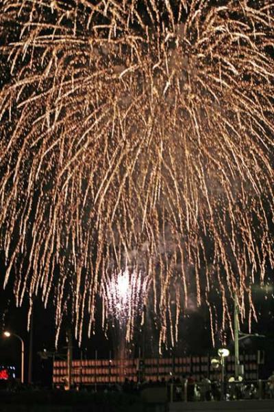 ちょうちんの後ろで大量の打ち上げ花火