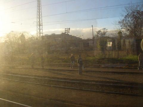 線路わきで列車を待つ人々。