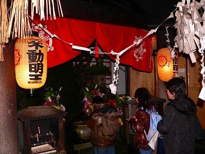 写真キャプション=大阪・法善寺横町の水掛不動にお参りをする人々