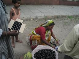 デリーの木下に座っているフルーツ売りは何?